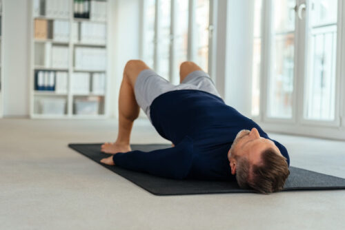 Man doing exercises lying on back in office